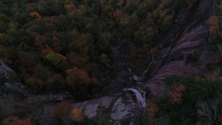 CAP_014_017 - 2.7K stock footage aerial video a bird's eye view of forest under a clifftop waterfall at sunset, Chimney Rock, North Carolina