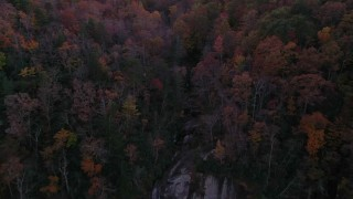 CAP_014_018 - 2.7K stock footage aerial video a reverse view of forest, reveal a clifftop waterfall at sunset, Chimney Rock, North Carolina