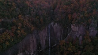 CAP_014_019 - 2.7K stock footage aerial video a reverse view of forest and a clifftop waterfall at sunset, Chimney Rock, North Carolina