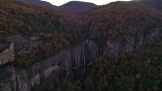 CAP_014_020 - 2.7K stock footage aerial video fly away from forest and a clifftop waterfall at sunset, Chimney Rock, North Carolina