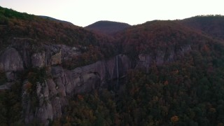 CAP_014_021 - 2.7K stock footage aerial video wide reverse view of forest and a clifftop waterfall at sunset, Chimney Rock, North Carolina
