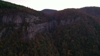 CAP_014_022 - 2.7K stock footage aerial video wide reverse view of forest, mountains, and a clifftop waterfall at sunset, Chimney Rock, North Carolina
