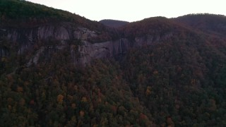 CAP_014_023 - 2.7K stock footage aerial video a view of forest, mountains, and a clifftop waterfall at sunset, Chimney Rock, North Carolina