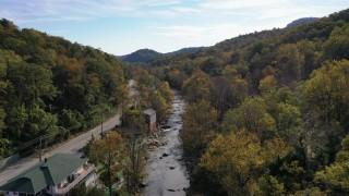 CAP_014_026 - 2.7K stock footage aerial video follow river over a bridge next to a road, Chimney Rock, North Carolina