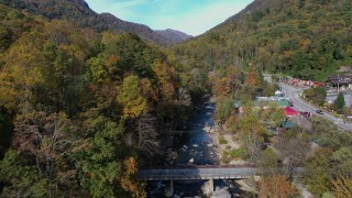 CAP_014_027 - 2.7K stock footage aerial video follow river over a bridge next to small town, Chimney Rock, North Carolina