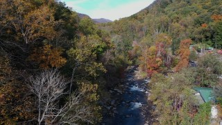 CAP_014_028 - 2.7K stock footage aerial video follow river surrounded by forest trees, Chimney Rock, North Carolina