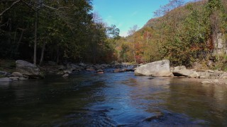 CAP_014_029 - 2.7K stock footage aerial video flying low over the river surrounded by forest trees, Chimney Rock, North Carolina