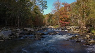 CAP_014_030 - 2.7K stock footage aerial video flying low over rocks and water in the river surrounded by forest trees, Chimney Rock, North Carolina