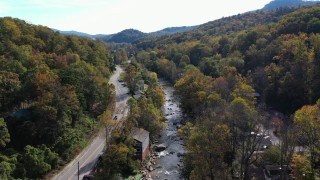 CAP_014_031 - 2.7K stock footage aerial video follow river beside a road through town, Chimney Rock, North Carolina