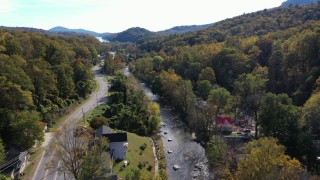 CAP_014_032 - 2.7K stock footage aerial video of flying over a river beside a road through a small town, Chimney Rock, North Carolina