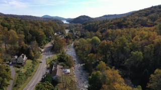 CAP_014_033 - 2.7K stock footage aerial video of flying over a river beside a road in a small town, Chimney Rock, North Carolina