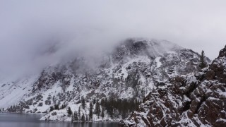 CAP_015_002 - 4K stock footage aerial video of panning across snowy mountain slopes beside lake in Inyo National Forest, California