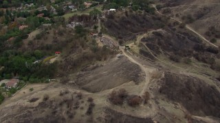 CAP_018_004 - HD stock footage aerial video of flying above burned hills toward destroyed homes in Malibu, California
