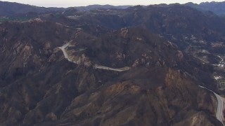 CAP_018_015 - HD stock footage aerial video of road and tunnels by mountains scarred by fire, Malibu, California