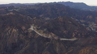 CAP_018_016 - HD stock footage aerial video of flying by road and tunnels by mountains scarred by fire, Malibu, California