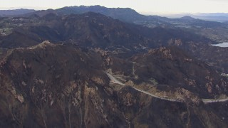 CAP_018_017 - HD stock footage aerial video of passing road and tunnels by mountains scarred by fire, Malibu, California