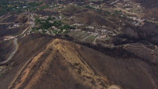CAP_018_019 - HD stock footage aerial video of flying over a mountain scarred by fire to approach destroyed homes, Malibu, California
