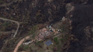 CAP_018_024 - HD stock footage aerial video of orbiting a hillside home destroyed by fire, Malibu, California