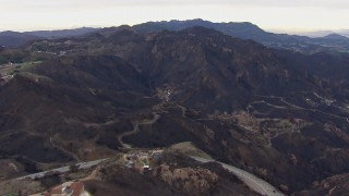 CAP_018_027 - HD stock footage aerial video reverse view of hillside homes destroyed by fire by scorched mountains, Malibu, California