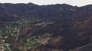 CAP_018_028 - HD stock footage aerial video of approaching homes destroyed by fire by scorched mountains, Malibu, California