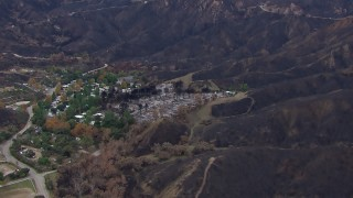 CAP_018_029 - HD stock footage aerial video of flying toward homes destroyed by fire by scorched mountains, Malibu, California
