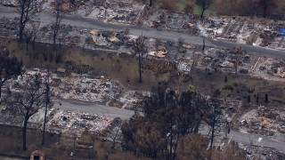CAP_018_032 - HD stock footage aerial video of a close-up view of a neighborhood destroyed by fire, Malibu, California