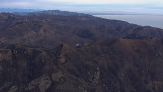 CAP_018_040 - HD stock footage aerial video of approaching mountains scorched by fire, Malibu, California