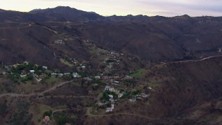 CAP_018_042 - HD stock footage aerial video of mountains scorched by fire near hillside homes, Malibu, California