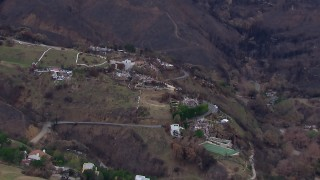 CAP_018_044 - HD stock footage aerial video of flying toward homes destroyed by fire, Malibu, California