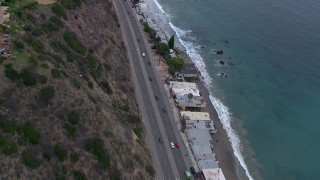 CAP_018_060 - HD stock footage aerial video of following light traffic on PCH at sunset, flyby Malibu homes, California