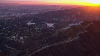 CAP_018_081 - HD stock footage aerial video of a view of the city while orbiting radio towers atop Hollywood Hills at sunset, California
