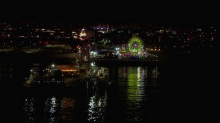 CAP_018_122 - HD stock footage aerial video flying over the ocean to approach the Ferris wheel and rides at nighttime, Santa Monica Pier, California