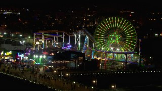 CAP_018_123 - HD stock footage aerial video flying around the Ferris wheel and rides at nighttime, Santa Monica Pier, California