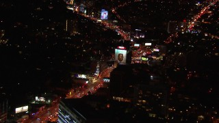 CAP_018_126 - HD stock footage aerial video approach billboard by the Sunset Strip at night in West Hollywood, California