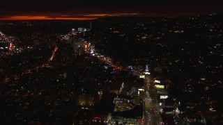 CAP_018_137 - HD stock footage aerial video approach Sunset Strip and tilt to billboards and traffic at night in West Hollywood, California