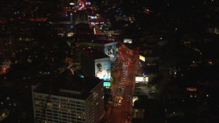 CAP_018_140 - HD stock footage aerial video tilt to and fly over Sunset Strip billboards and traffic at night in West Hollywood, California