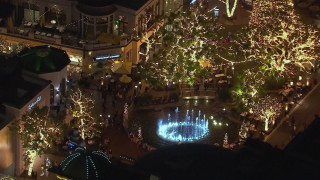 CAP_018_150 - HD stock footage aerial video of an orbit around a fountain at The Grove shopping mall at night in Los Angeles, California