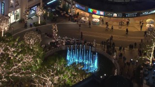 CAP_018_156 - HD stock footage aerial video of orbiting fountain at The Grove shopping mall, decorated for the holidays at night in Los Angeles, California