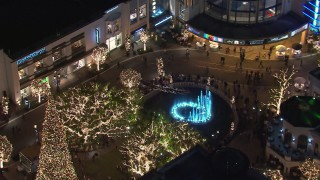 CAP_018_163 - HD stock footage aerial video of orbiting Christmas decorations and fountain at The Grove shopping mall at night in Los Angeles, California