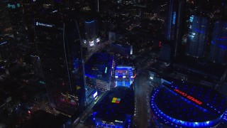 CAP_018_195 - HD stock footage aerial video orbit ice skating rink by theater and Ritz-Carlton at night, Downtown Los Angeles, California