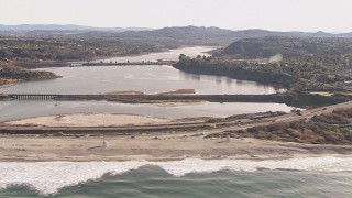 CAP_021_012 - HD stock footage aerial video passing by a lagoon and coastal highway by a beach, Encinitas, California