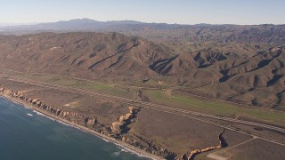 CAP_021_041 - HD stock footage aerial video of I-5 between mountains and coastal cliffs, San Clemente, California
