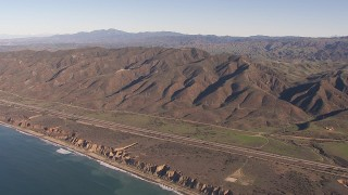 CAP_021_042 - HD stock footage aerial video of flying by I-5 between mountains and coastal cliffs, San Clemente, California