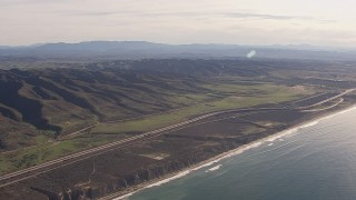 CAP_021_043 - HD stock footage aerial video of a reverse view of I-5 between mountains and coastal cliffs, San Clemente, California
