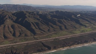 CAP_021_044 - HD stock footage aerial video of panning across I-5 between mountains and coastal cliffs, San Clemente, California