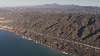 CAP_021_045 - HD stock footage aerial video of panning across I-5 between mountains and coastal cliffs to reveal nuclear plant, San Clemente, California
