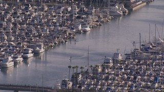 CAP_021_064 - HD stock footage aerial video orbit people paddling between yachts and sailboats at the harbor in Dana Point, California