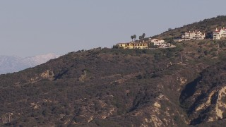 CAP_021_065 - HD stock footage aerial video flyby hillside mansions to focus on distant snowy mountains in Dana Point, California