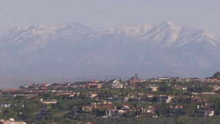 CAP_021_073 - HD stock footage aerial video of distant snowy mountains seen from hilltop mansions, Laguna Beach, California