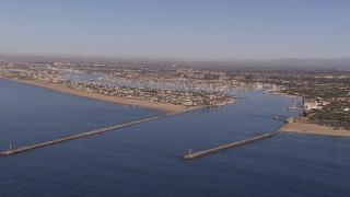 CAP_021_074 - HD stock footage aerial video of flying by the inlet to the bay by coastal neighborhoods, Newport Beach, California